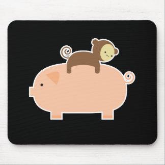 Équitation de singe de bébé sur un porc tapis de souris