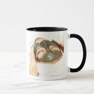 Esthéticien qui frotte le paquet de boue sur le mug