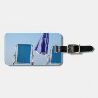 Étiquette À Bagage Deux chaises et parasols de plage bleus à sea.JPG