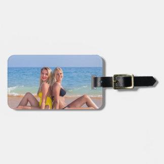 Étiquette À Bagage Deux filles s'asseyent sur la plage près de