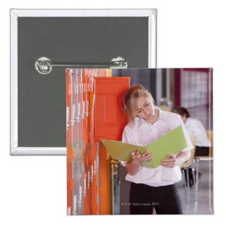 Étudiant enlevant le classeur du casier d'école badges