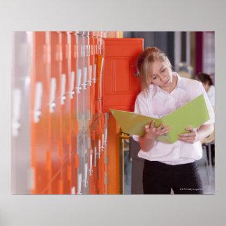 Étudiant enlevant le classeur du casier d'école posters