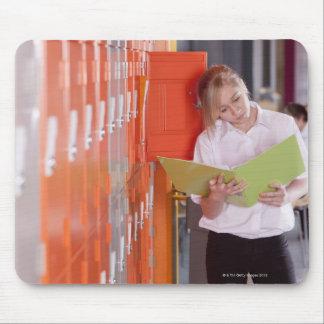 Étudiant enlevant le classeur du casier d'école tapis de souris