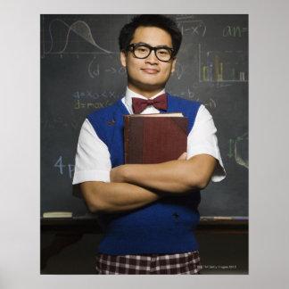Étudiant masculin asiatique ringard tenant le livr posters