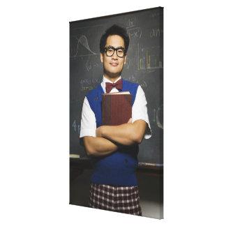 Étudiant masculin asiatique ringard tenant le livr toile tendue sur châssis