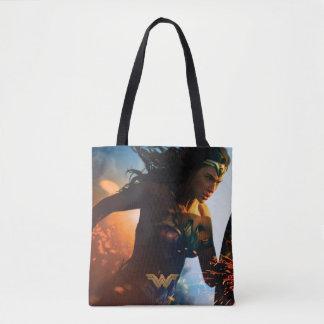 Femme de merveille courant sur le champ de sac