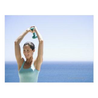 femme excercising avec des poids sur son toit carte postale