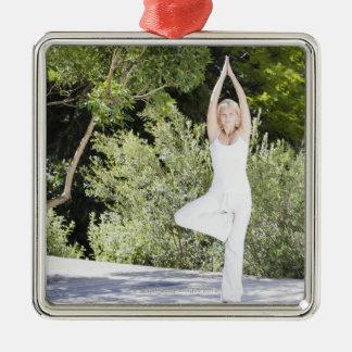Femme faisant le yoga sur le patio ornement carré argenté