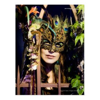 Femme portant un masque regardant de et le fer carte postale