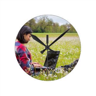 Femme s'asseyant avec le pré d'ordinateur portable horloge ronde