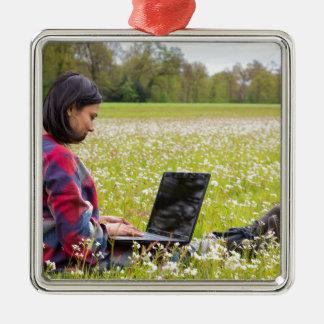 Femme s'asseyant avec le pré d'ordinateur portable ornement carré argenté