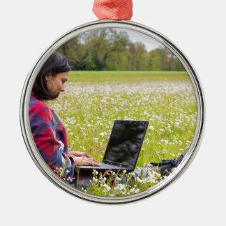 Femme s'asseyant avec le pré d'ordinateur portable ornement rond argenté