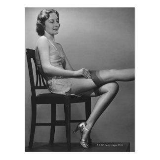 Femme s'asseyant sur la chaise carte postale