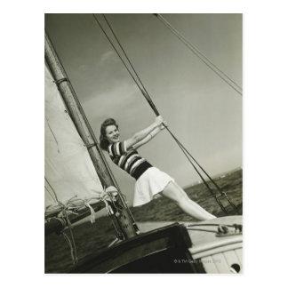 Femme tenant le calage sur le yacht cartes postales