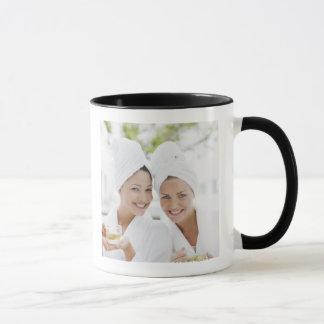 Femmes dans des peignoirs buvant du thé au spa mug