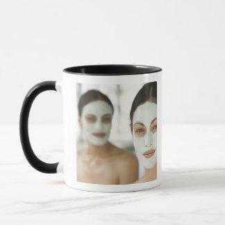 Femmes souriant dans des masques de boue de beauté mugs