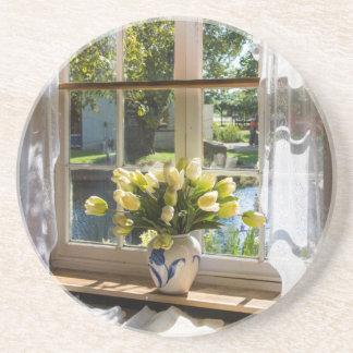 Fenêtre avec le rideau et les tulipes en dentelle dessous de verre