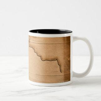 Fermez-vous de la carte antique du monde avec mug bicolore