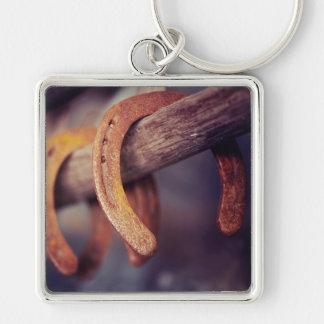 Fers à cheval sur le pays en bois de cowboy de porte-clé carré argenté