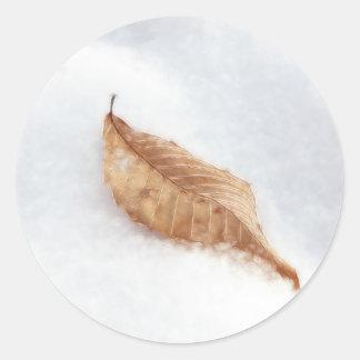 Feuille de hêtre dans une dérive de neige sticker rond