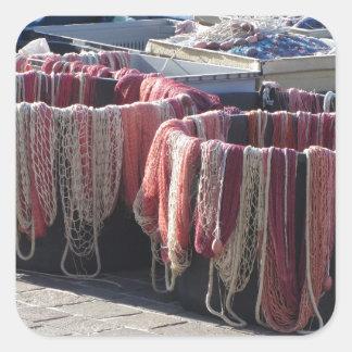 Filets de pêche colorés dans le port. La Toscane Sticker Carré