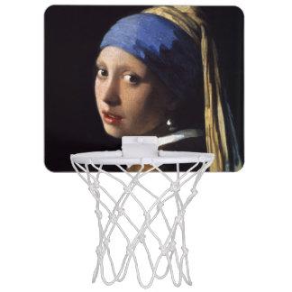 Fille avec une boucle d'oreille de perle par mini-panier de basket
