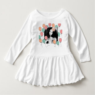 Fille mignonne avec la fleur dans ses cheveux robe manches longues