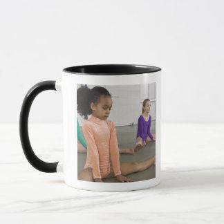 Filles s'étirant dans la pratique en matière de mugs