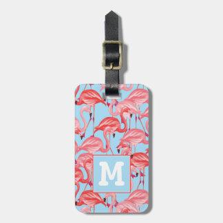 Flamants roses lumineux sur le monogramme du bleu étiquette à bagage