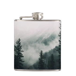 Flasques Au-dessus des montagnes et de la cuvette les bois