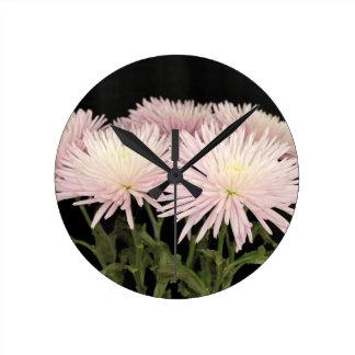 Fleurs blanches violettes de chrysanthème sur le horloge ronde