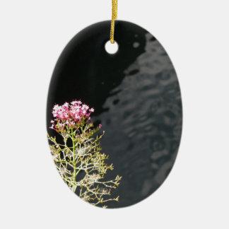 Fleurs sauvages contre la surface de l'eau d'une ornement ovale en céramique