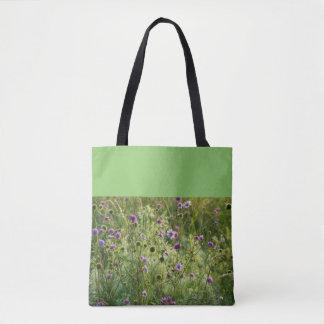 Fleurs sauvages pourpres dans un pré vert sac