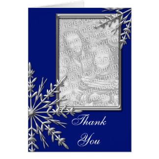 Flocon de neige argenté sur le carte photo bleu de