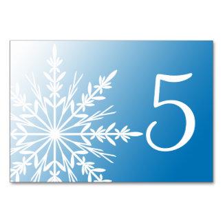 Flocons de neige blancs sur des nombres bleus de