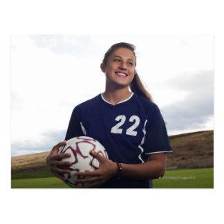 footballeur de l'adolescence de fille tenant le cartes postales