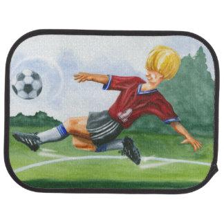 Footballeur donnant un coup de pied une boule par tapis de sol