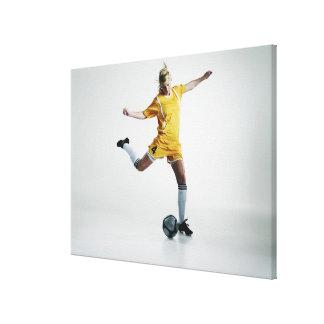 Footballeur féminin disposant à donner un coup de toiles