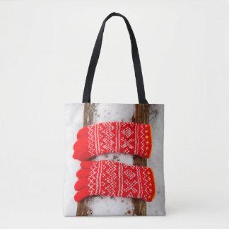 Gants tricotés par rouge dans la neige sac