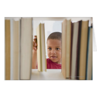 Garçon d'Afro-américain choisissant le livre Carte De Vœux