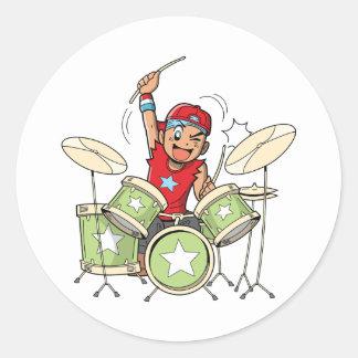 Garçon jouant des autocollants de tambours