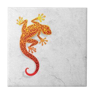 Gecko rouge s'élevant sur un mur blanc petit carreau carré