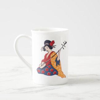 Geisha jouant une tasse de porcelaine tendre de