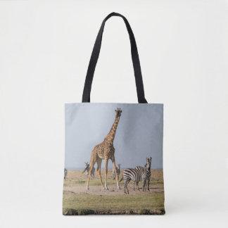 Girafe et zèbres par un point d'eau tote bag