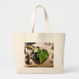 Grand Tote Bag Olives noires sur une table et des tasses en verre
