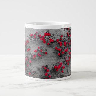 Grande Tasse les roses s'élèvent sur un mur de briques sur la