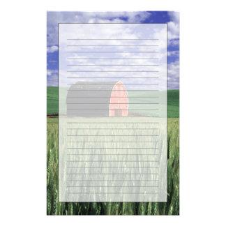 Grange rouge dans le domaine de blé et d'orge en papeterie
