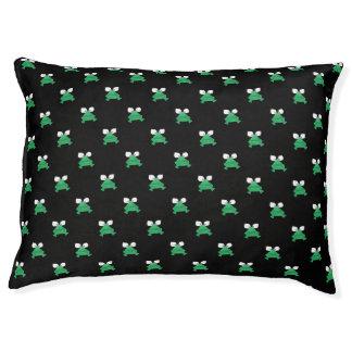 Grenouilles vertes sur le lit de chien noir