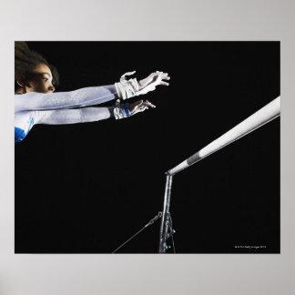 Gymnaste (9-10) atteignant pour les barres posters