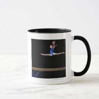 Gymnaste (9-10) sautant sur le faisceau mug